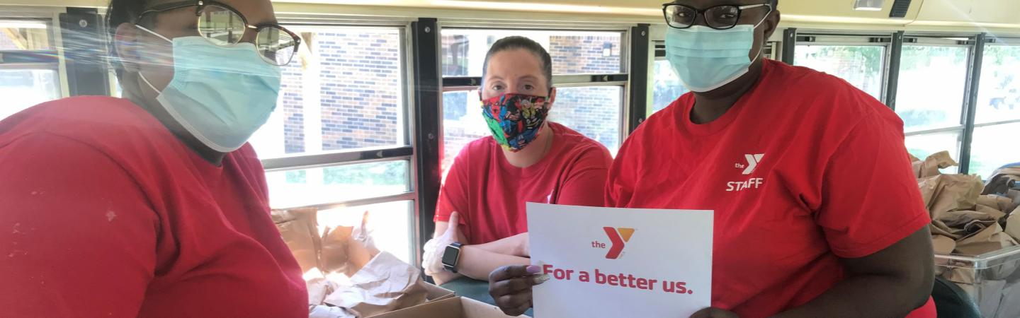 Y staff inside the bus filled with lunch bags for delivery to various Kalamazoo neighborhoods.